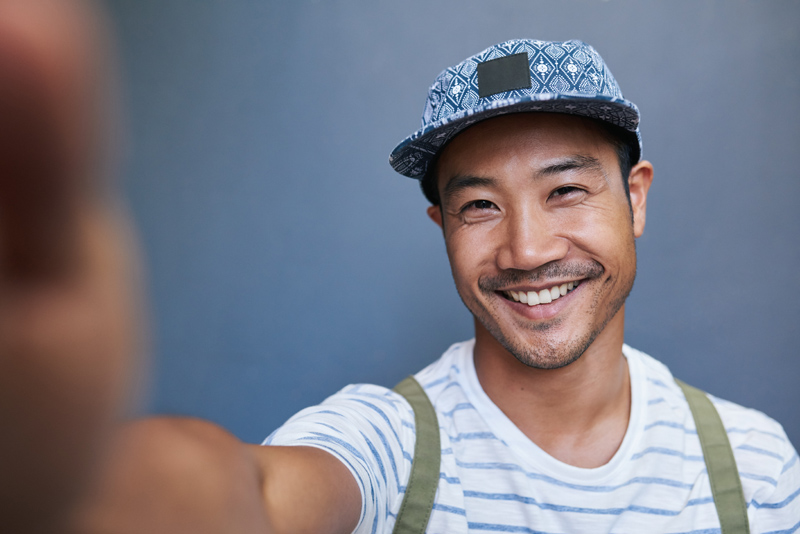 Portrait of a stylishly dressed young Asian man smiling and taking a selfie while standing alone in front of a gray wall outside