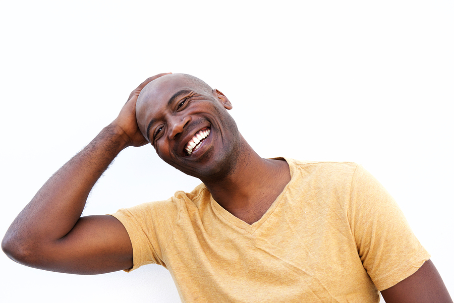 Close up portrait of smiling young african man against white background with his hand on head